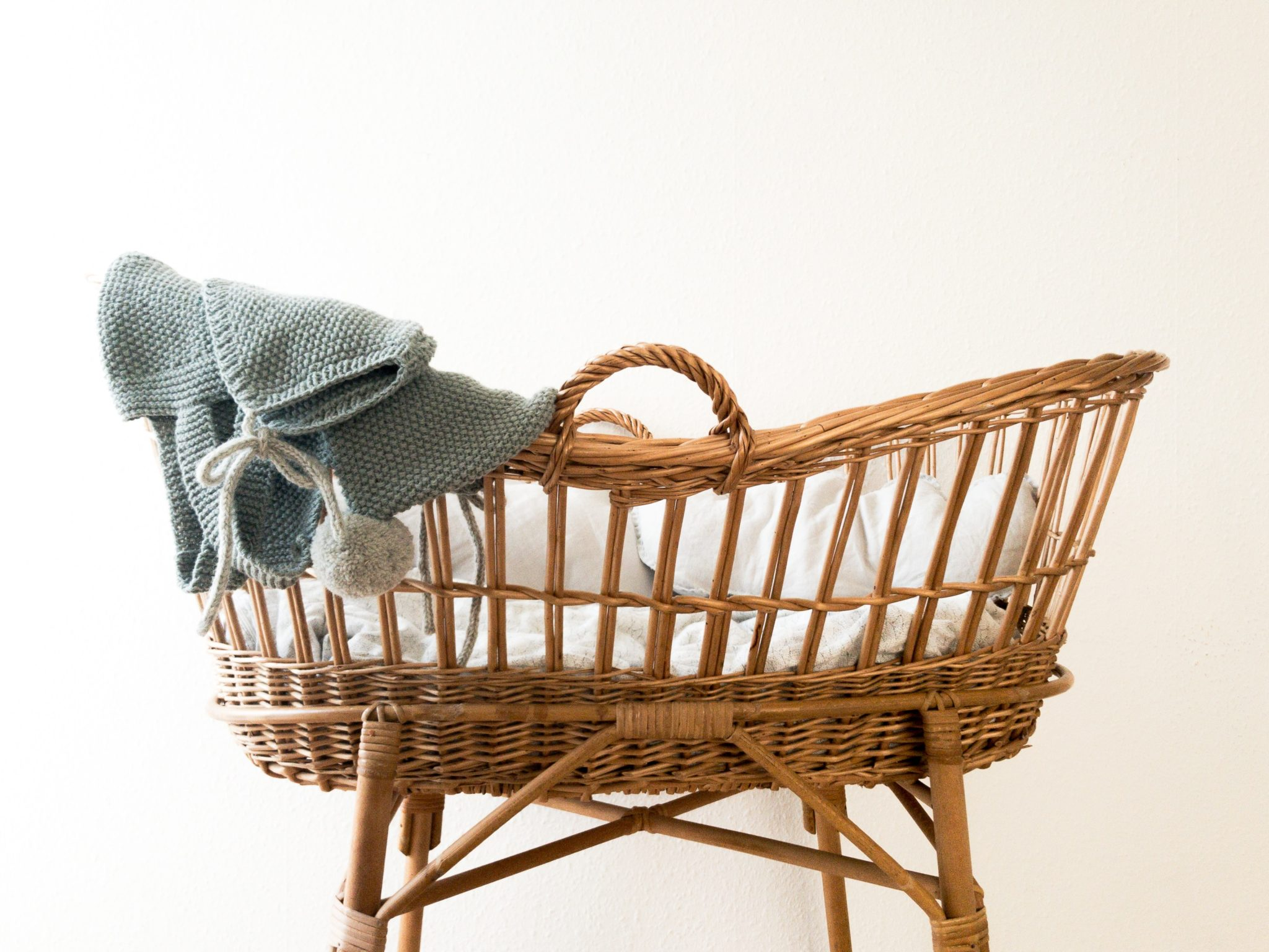 a wicker baby carriage with a blue blanket on top