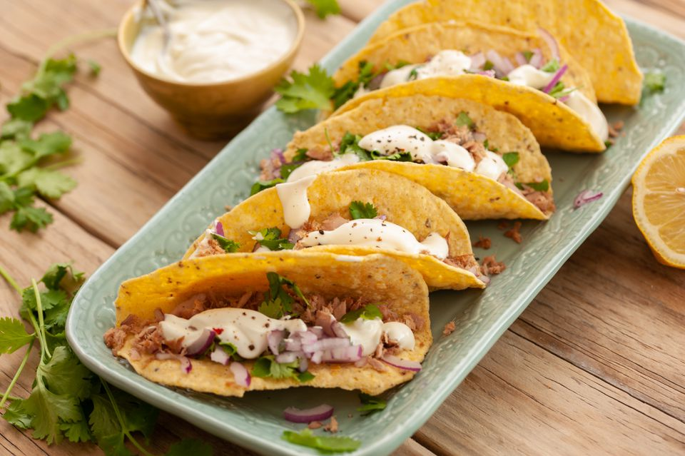 full shot image of five canned tuna fish tacos on a rectangular green plate garnished with fresh herbs and aioli
