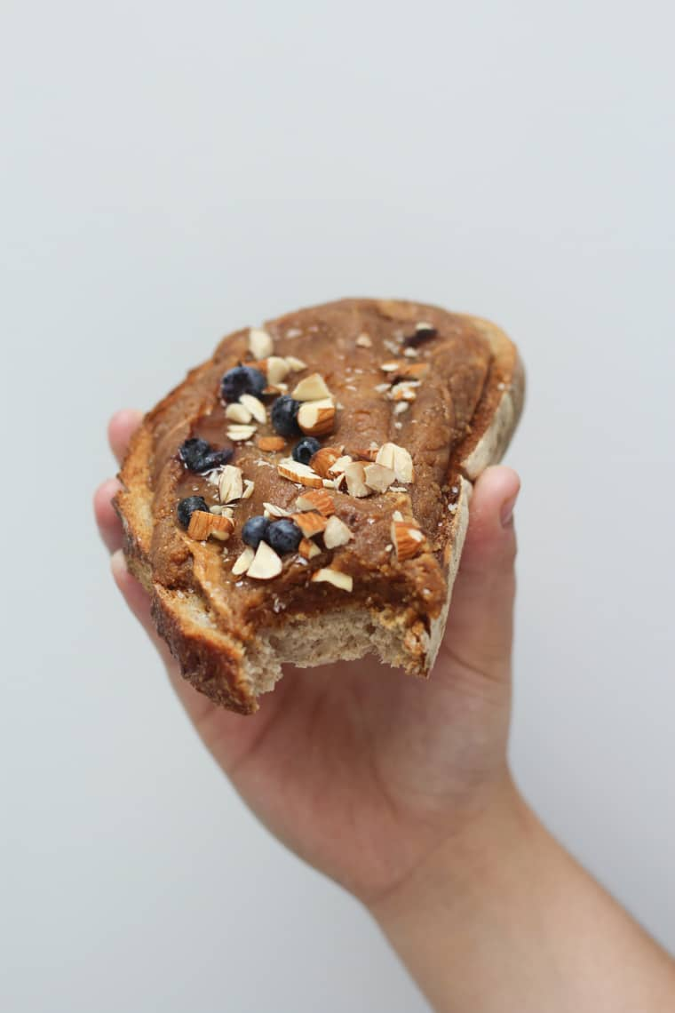close up image of a hand holding a piece of salted caramel almond butter on toast garnished with almonds and blueberries