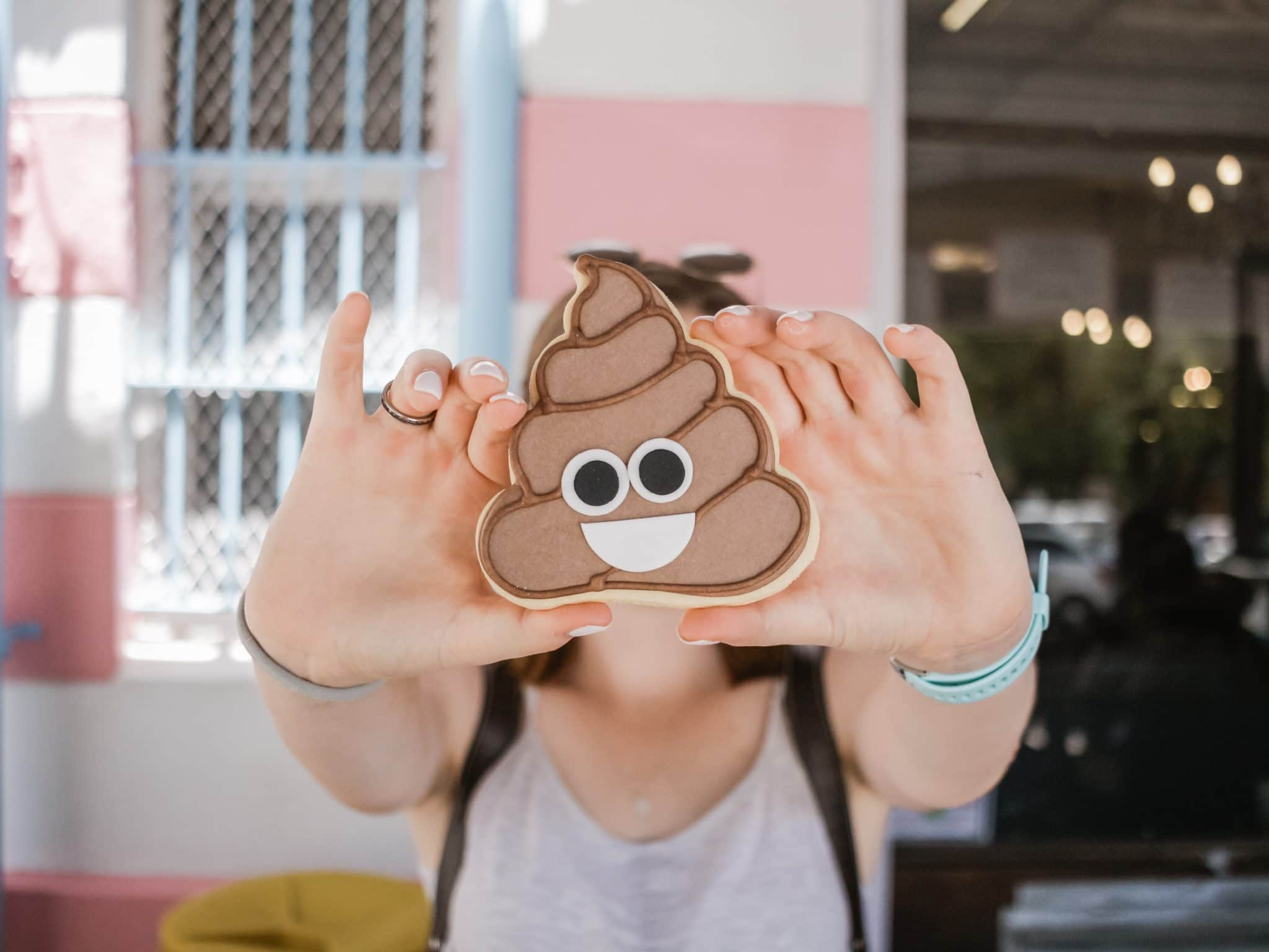 close up of a person holding a poop emoji symbol for gut health