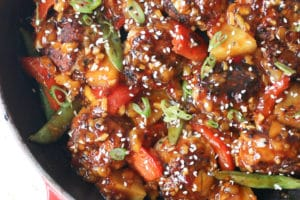 close up of one pan hawaiian chicken meatballs garnished with sesame seeds
