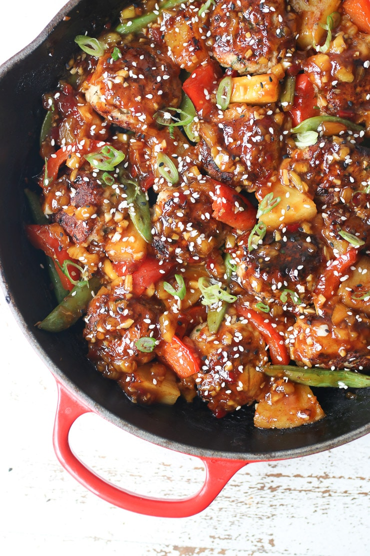 birds eye view of one pan hawaiian chicken meatballs in a black skillet garnished with sesame seeds