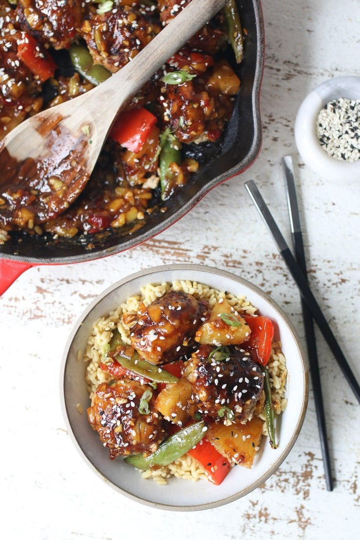 skillet hawaiian chicken meatballs on a white plate with chopsticks, sesame seed, and pot in the background