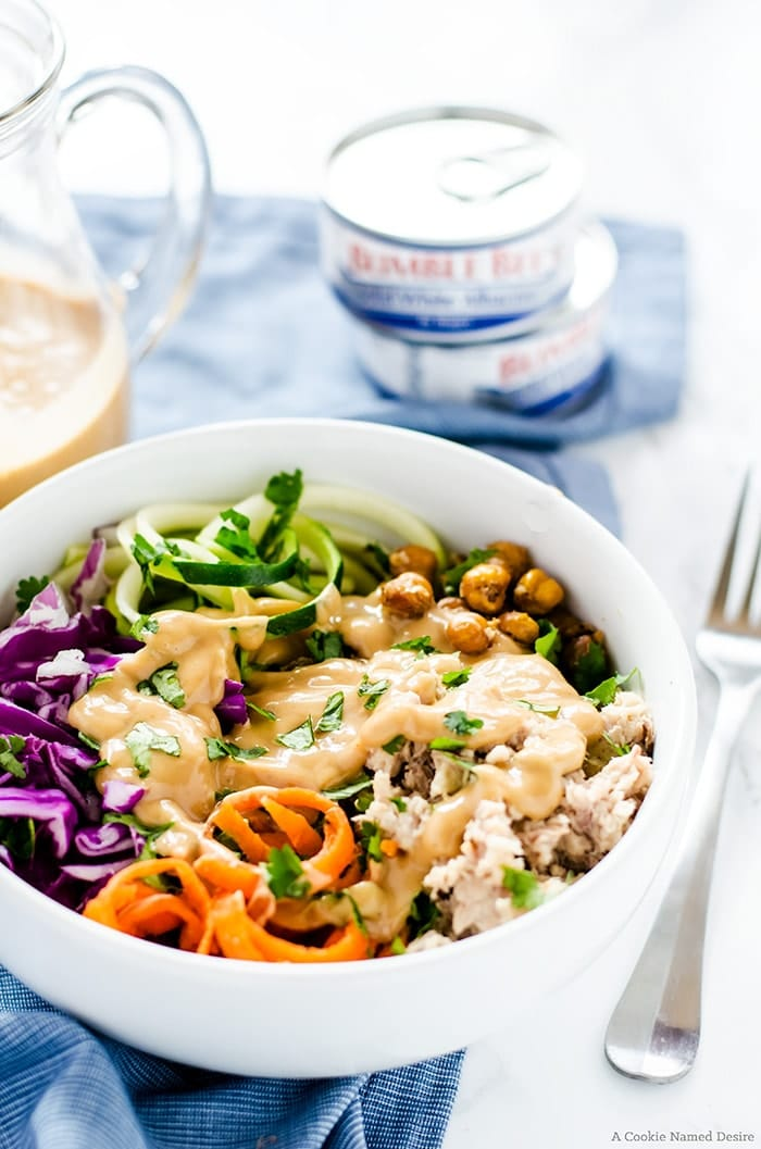 close up of thai tuna power bowl garnished with fresh herbs served in a white bowl with cans of tuna in the background