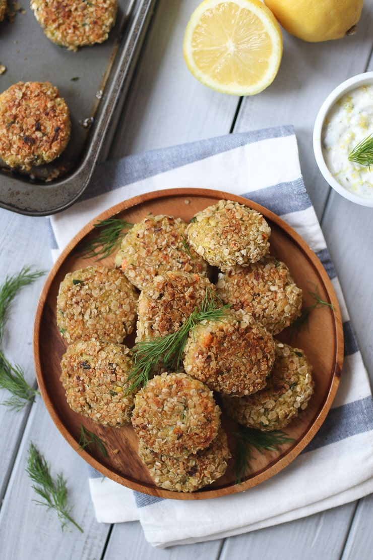 birds eye view multiple quinoa fish cakes garnished with fresh herbs on a wooden plate on a striped towel