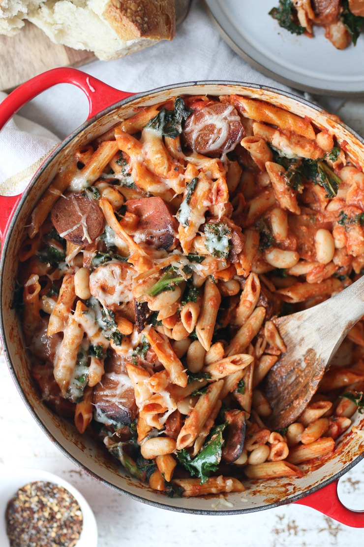 birds eye view of vegan pasta bake with beans and kale in a large red pot with a wooden stirring spoon inside
