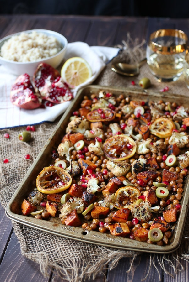 full shot image of chickpea and cauliflower dinner served on a sheet pan with pomegranate seeds, lemon, and cauliflower in the background