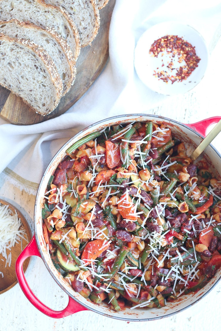 skillet minestrone pasta in a red pot with chili flakes and bread in the background