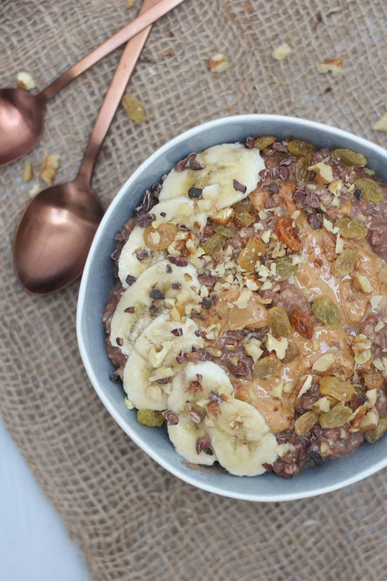 birds eye view of chocolate zucchini oatmeal in a blue bowl garnished with fresh and dried fruit with a rose gold spoon