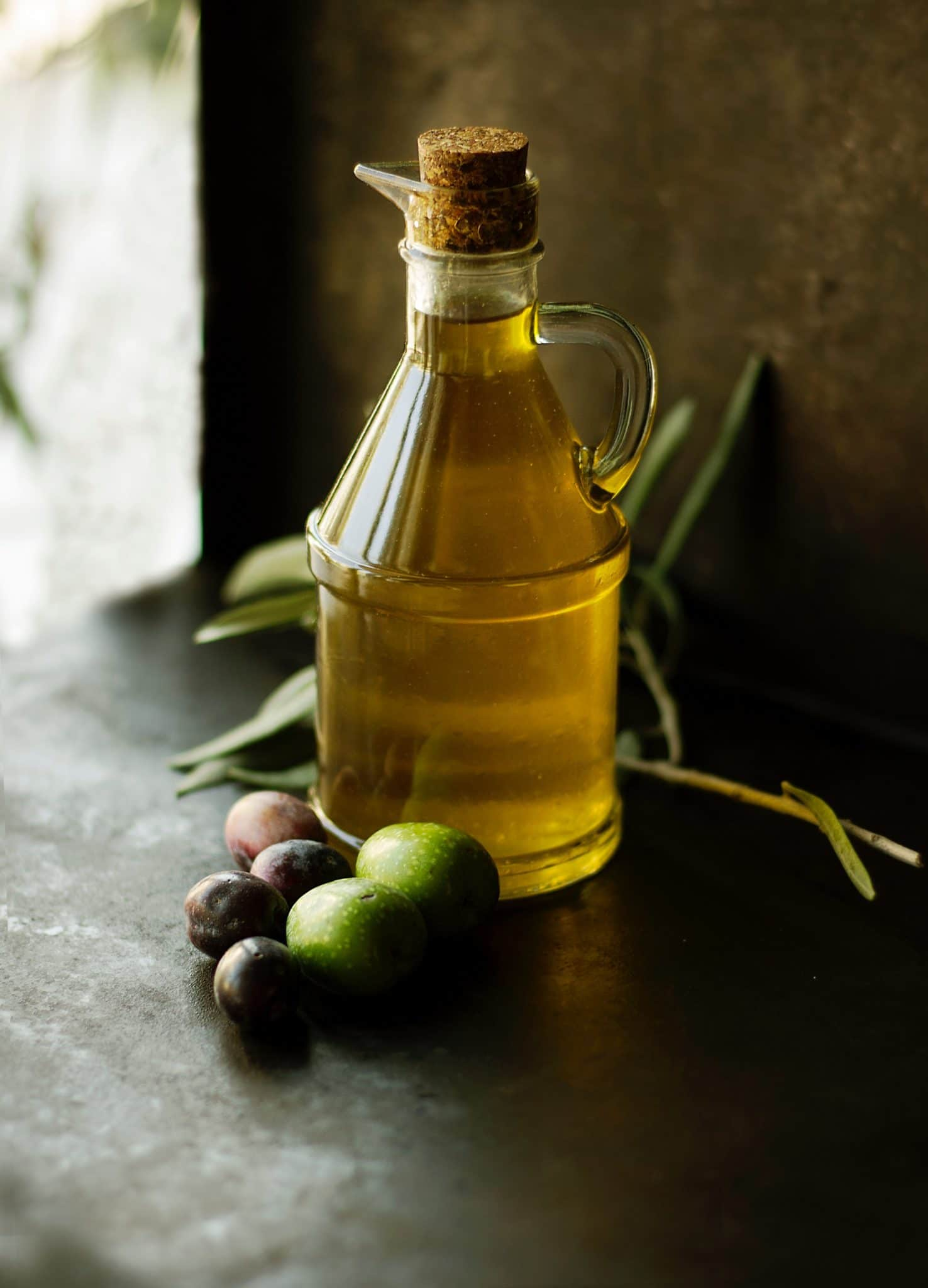 clear jug filled with olive oil on a wooden table next to a small bunch of fresh olives
