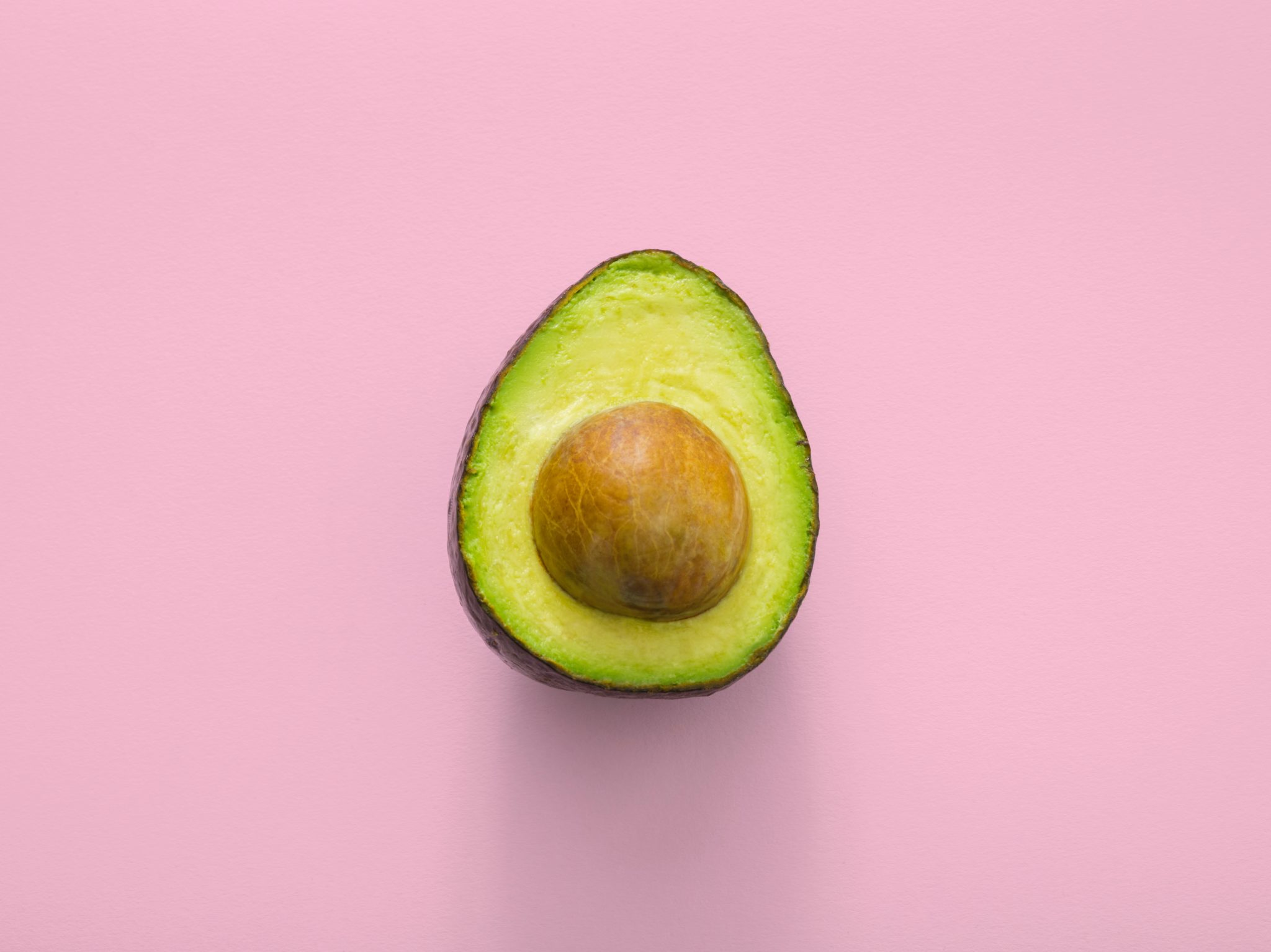 close up of half of a ripe avocado against a light pink background