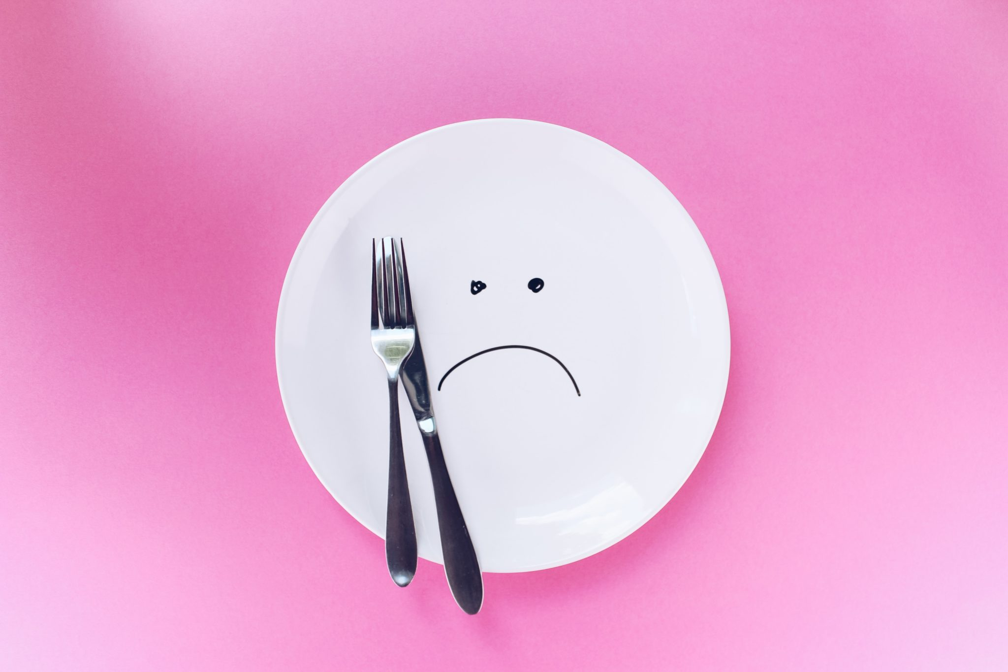 image of a plate with a sad face drawn on top next to a fork and knife against a pink background