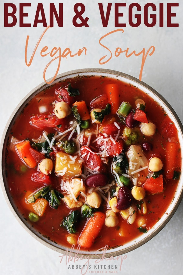 pinterest image of vegan soup made with beans and vegetables in a white bowl topped with vegan cheese with text overlay