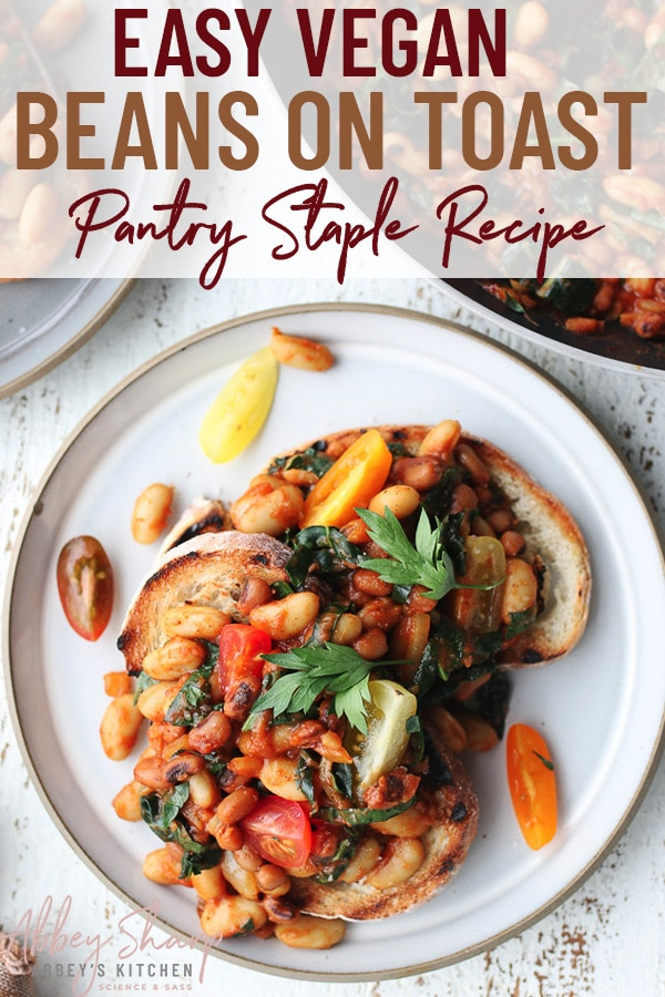 pinterest image of a birds eye shot of vegan pantry staple beans on toast garnished with tomatoes and fresh herbs with text overlay