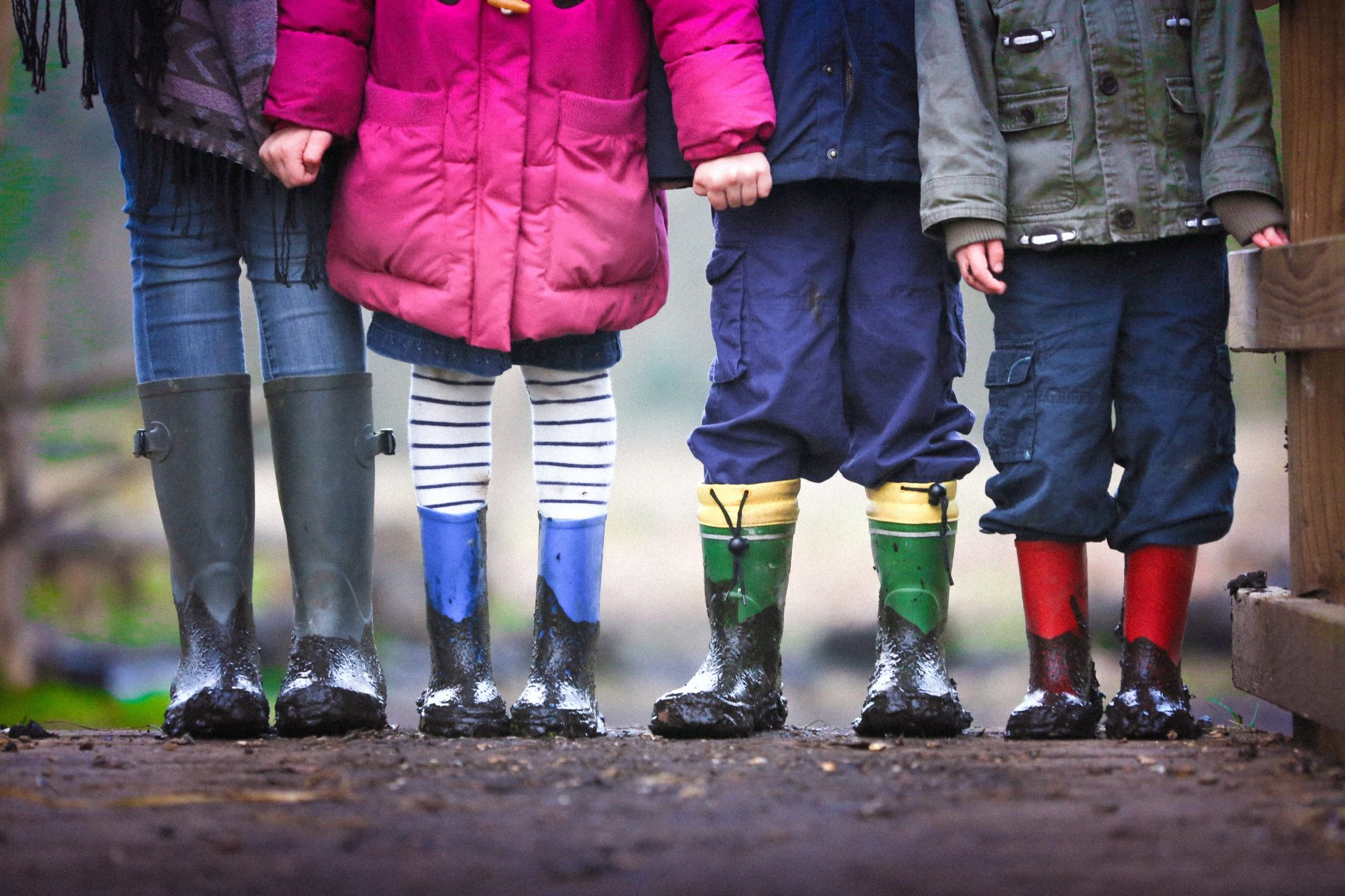 four children wearing rain boots standing side by side holding hands