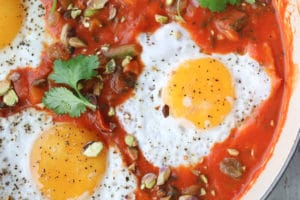 close up image of two eggs inside of curry spiced shakshuka garnished with fresh herbs gar