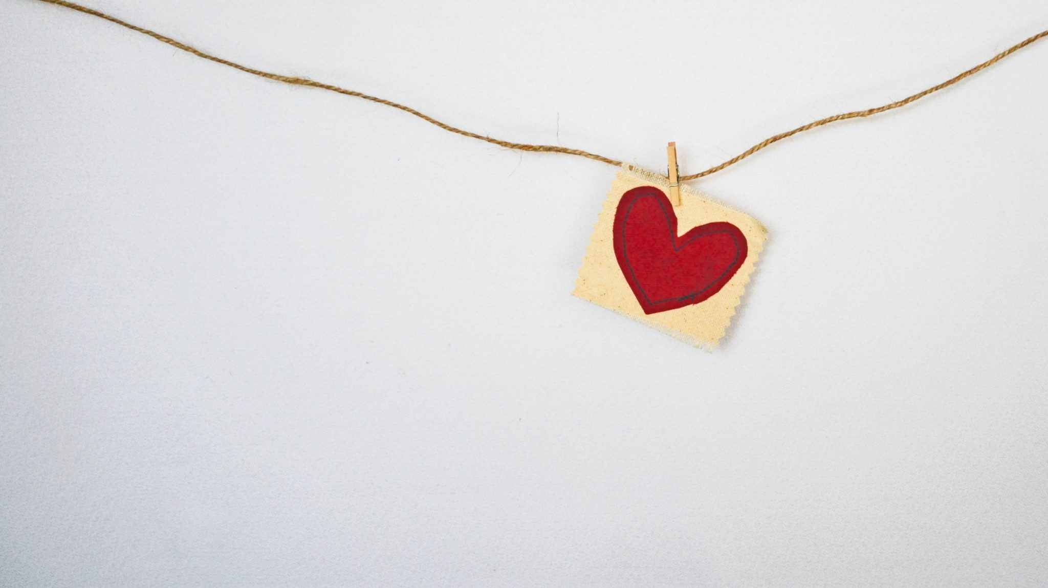 close up image of a red heart painting on a square canvas hanging from a rope against a white background