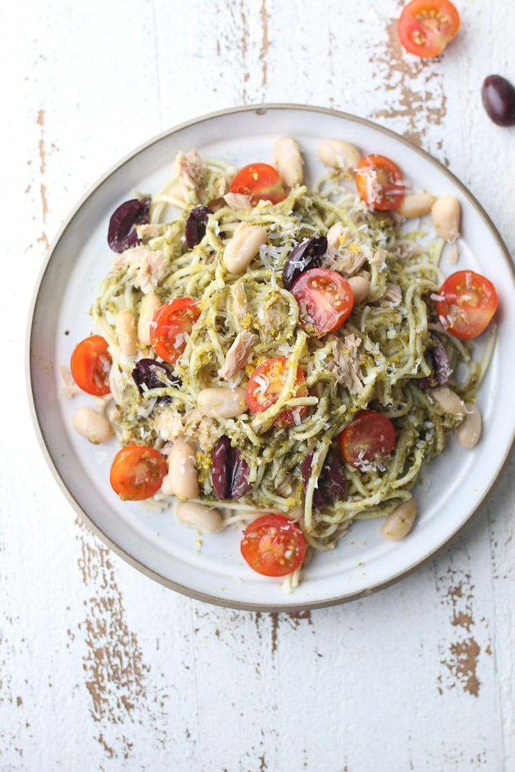 birds eye view of pesto pasta with tuna topped with beans, tomato and olives