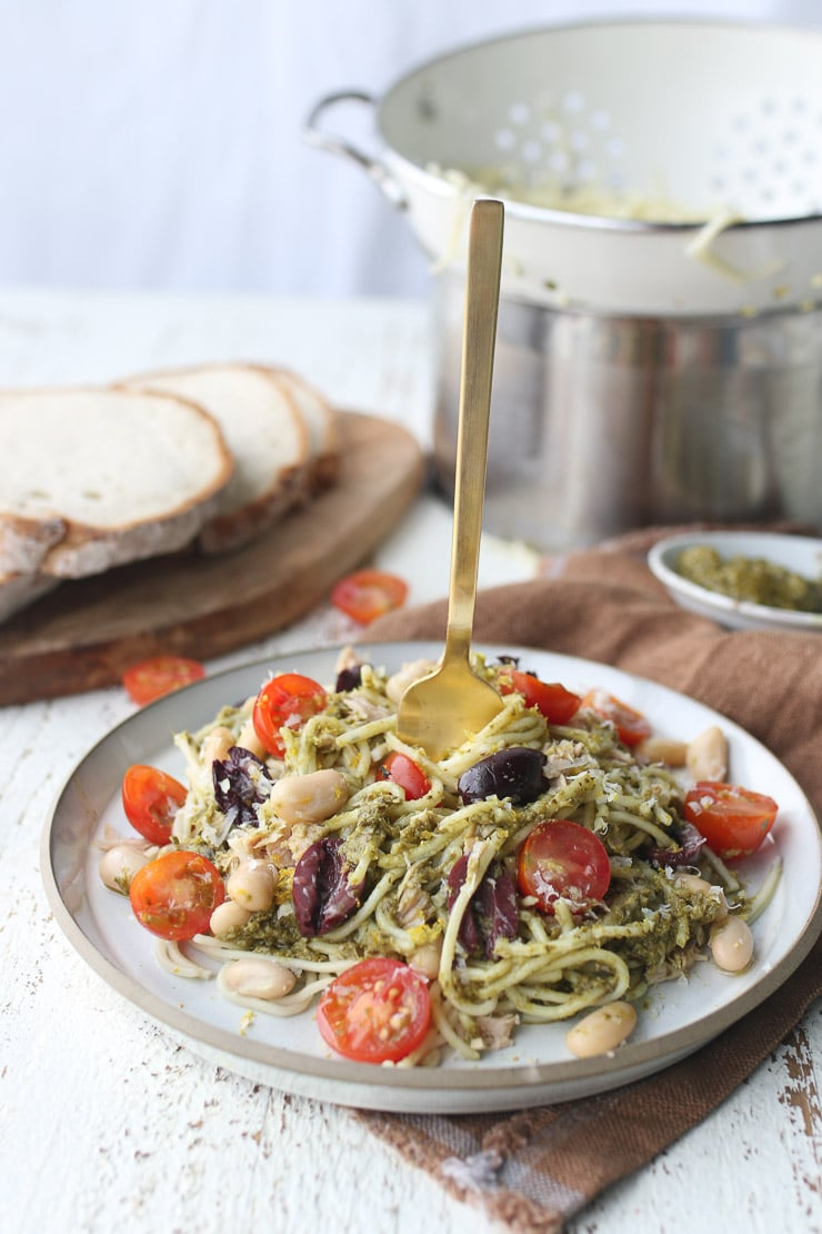 golden fork twirled into pesto pasta on a white plate
