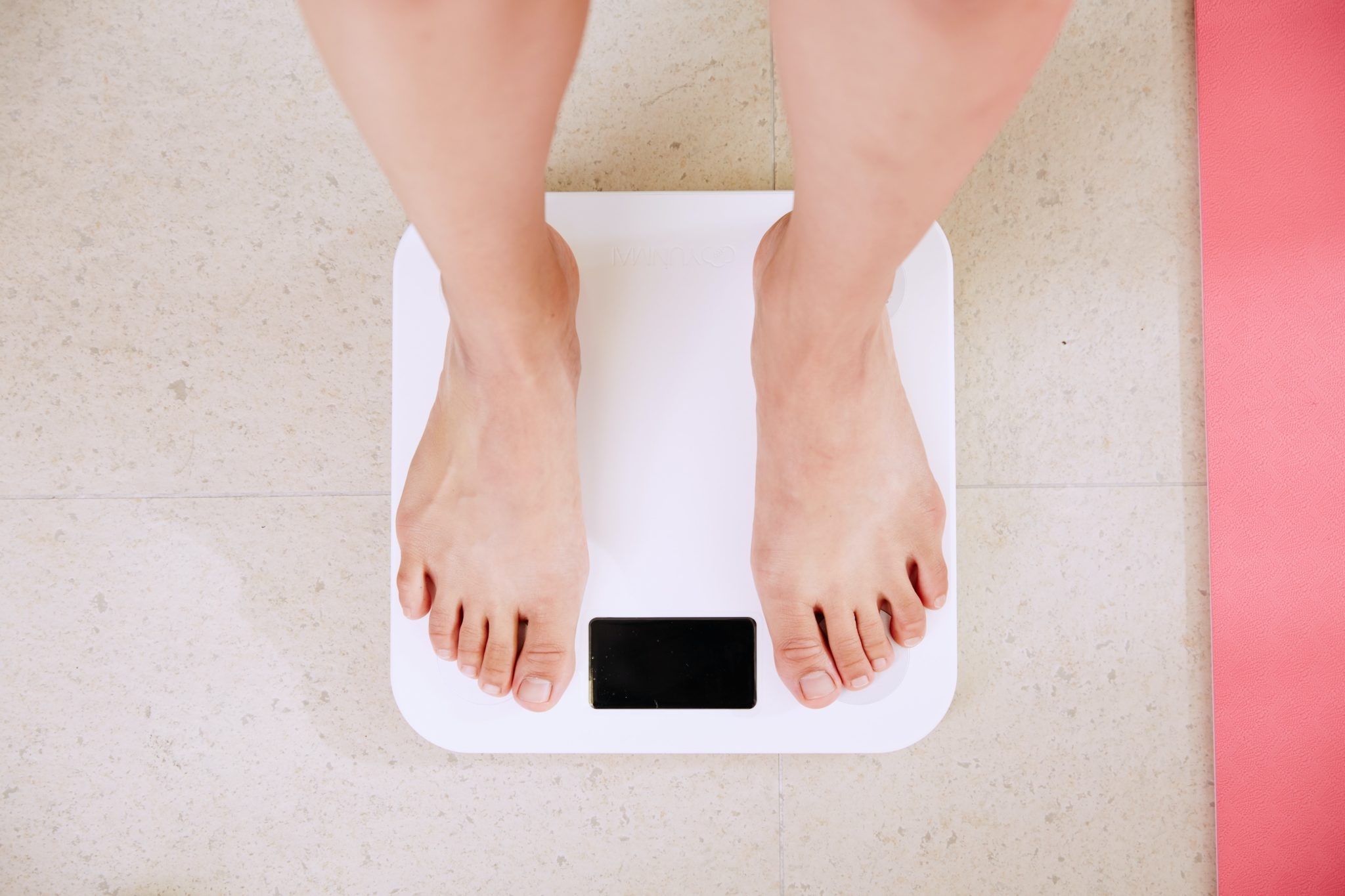 person standing on scale to measure body weight for bariatric surgery
