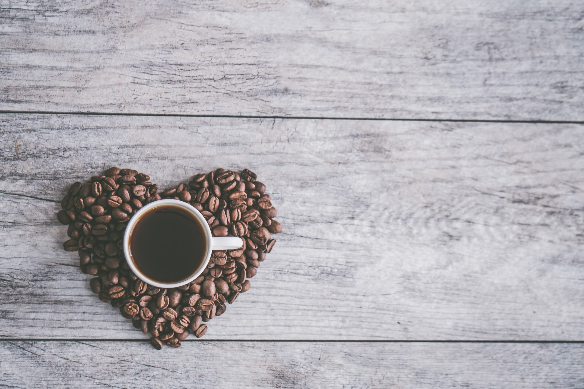 birds eye view of coffee beans in a heart shape with a mug of coffee in the centre against a wooden background