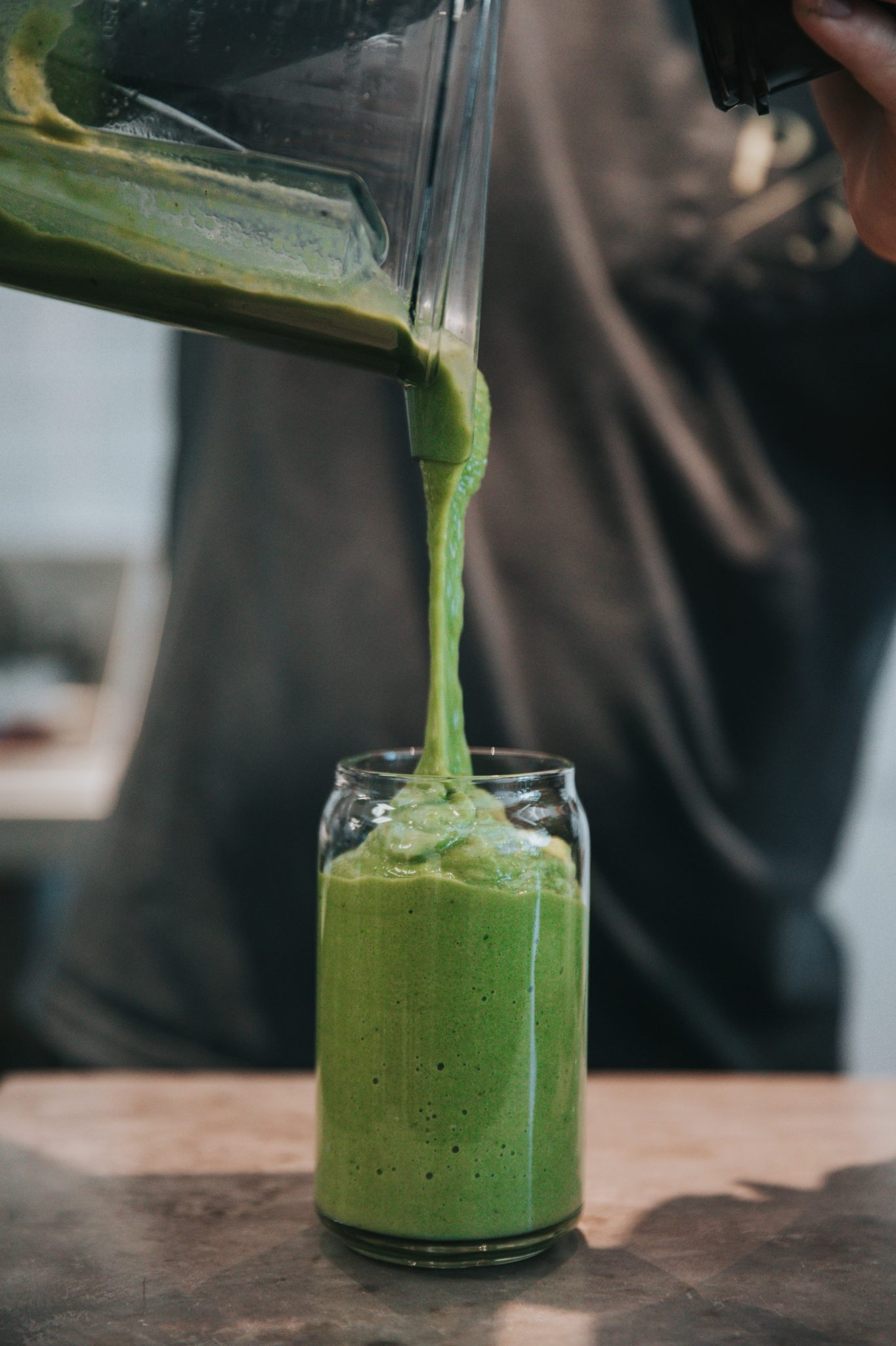 close up of a green smoothie being poured into a tall clear glass from a blender for bariatric surgery diet