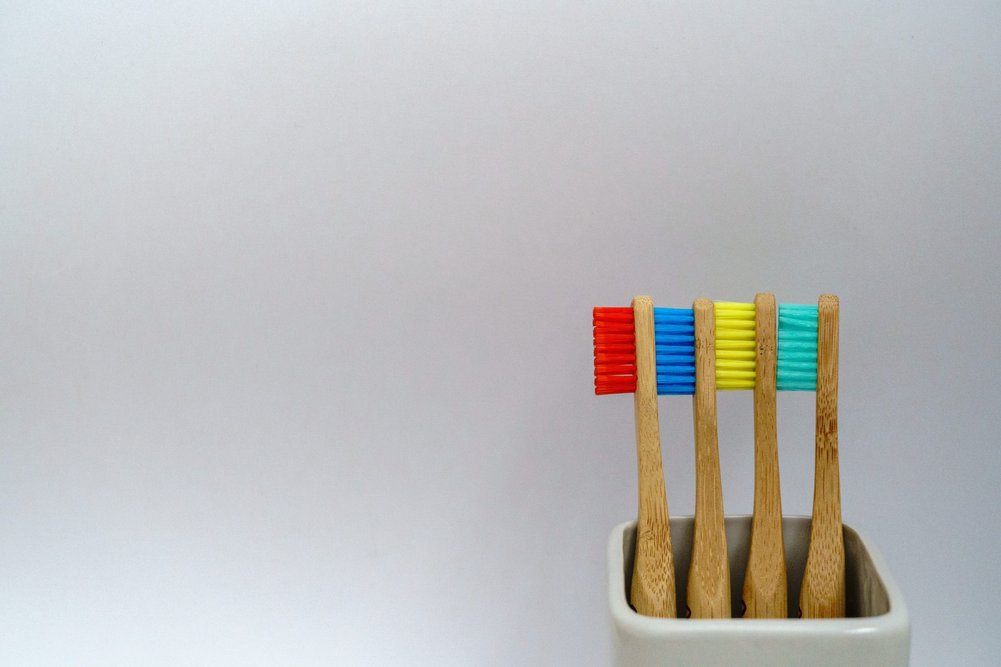 multiple wooden toothbrushes for children lined up against each other against a white background