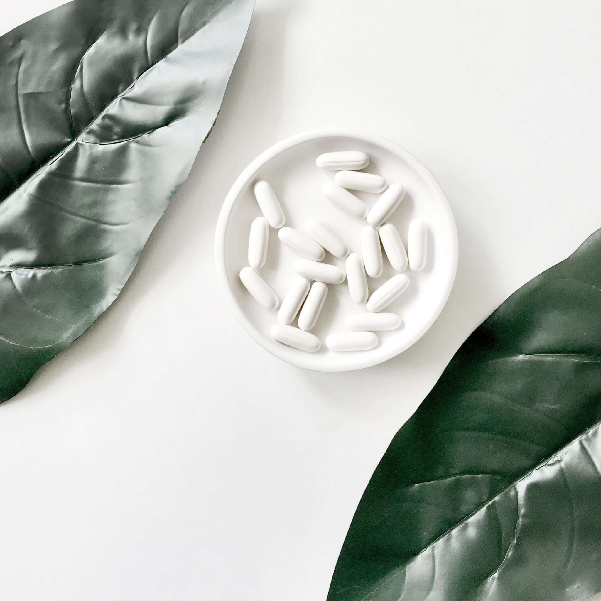 birds eye image of white fertility supplements in a white bowl against a white background with 2 green plants in the upper left and lower right corners