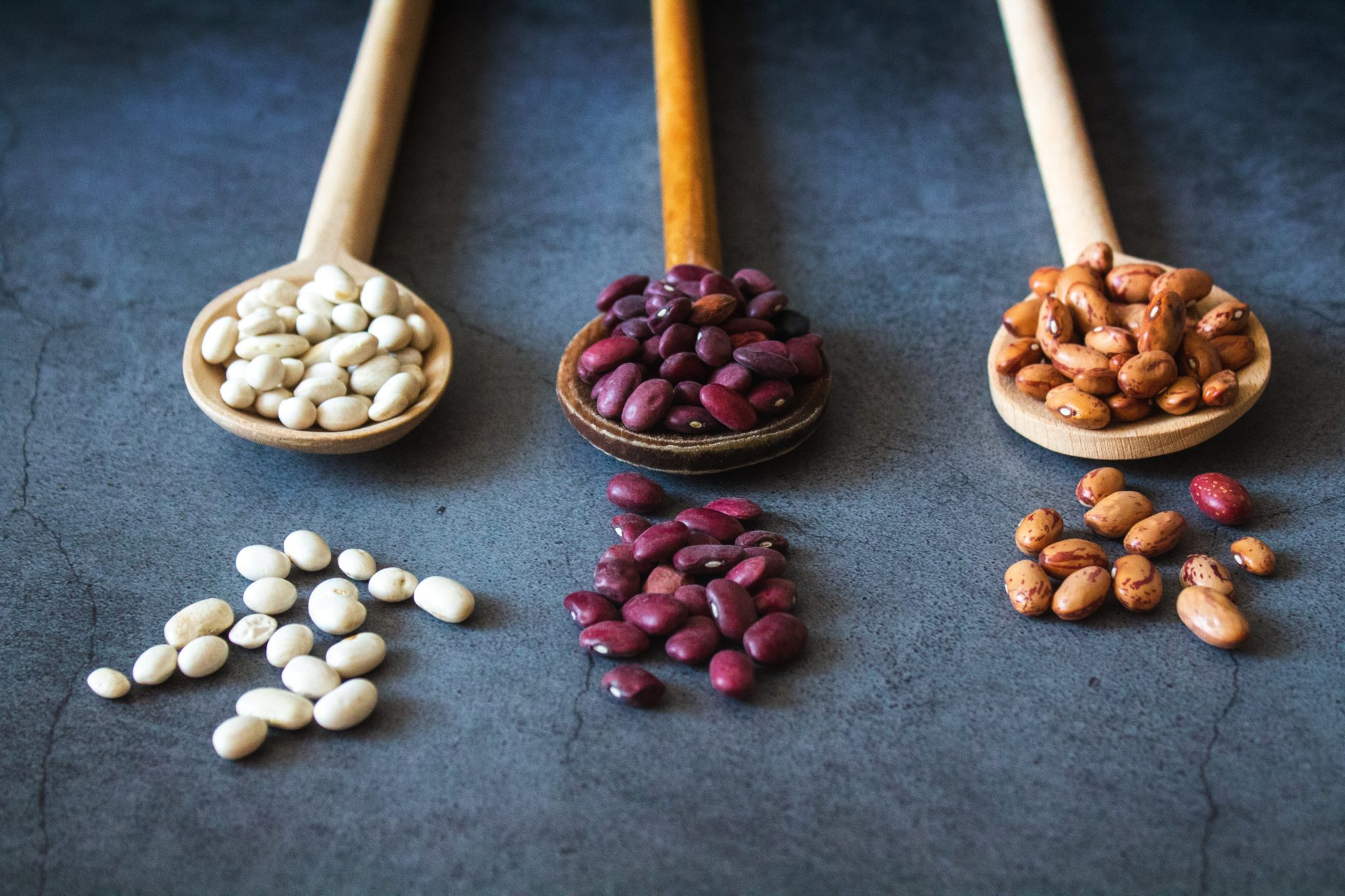 image of dried beans on wooden spoons to represent plant based protein foods that may assist with fertility