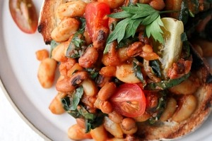 close up image of pantry stable navy beans on toast garnished with fresh cherry tomatoes and herbs on a white plate