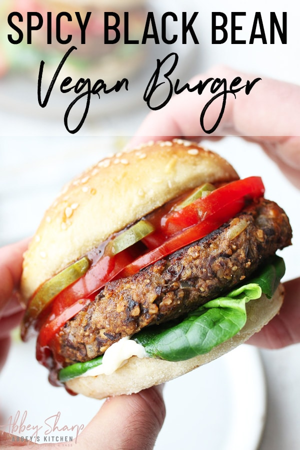pinterest image of a person holding vegetarian black bean burger inside of a sesame hamburger bun and an additional veggie burger in the background with text overlay in