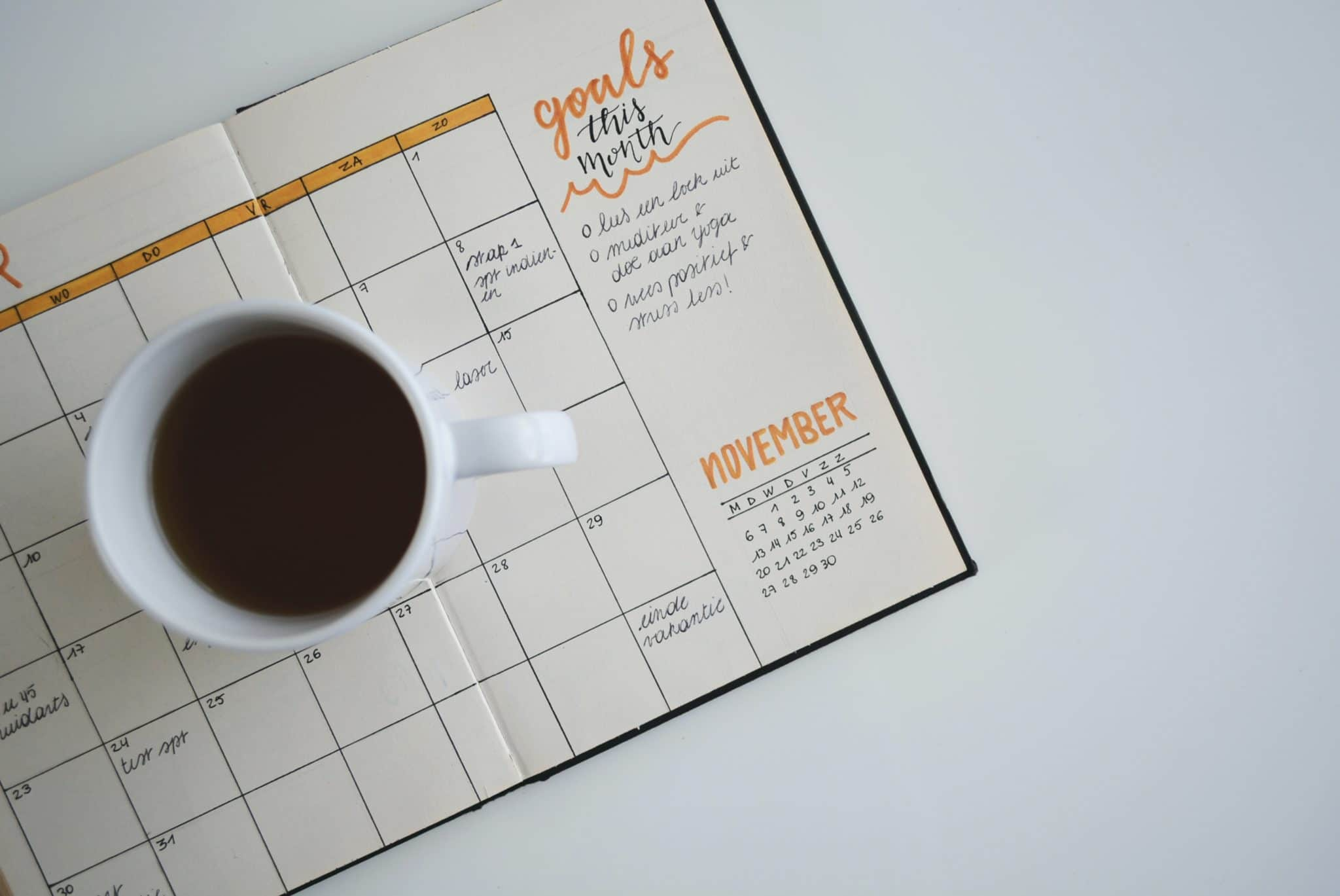 a day planner with a list of goals and a cup of coffee sitting on top