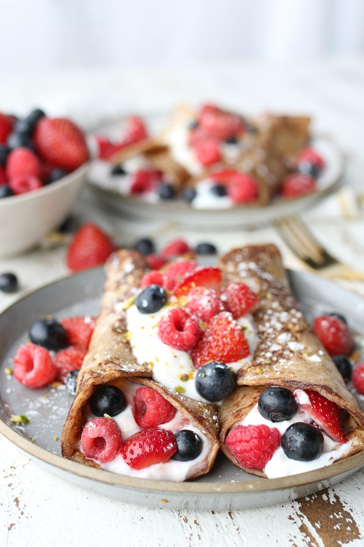 two french toast breakfast tortilla wraps stuffed with yogurt and berries on a grey plate