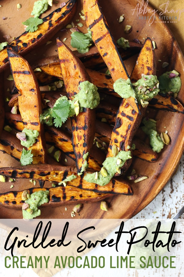 birdseye view of grilled sweet potato wedges on a brown plate topped with avocado sauce and garnished with cilantro