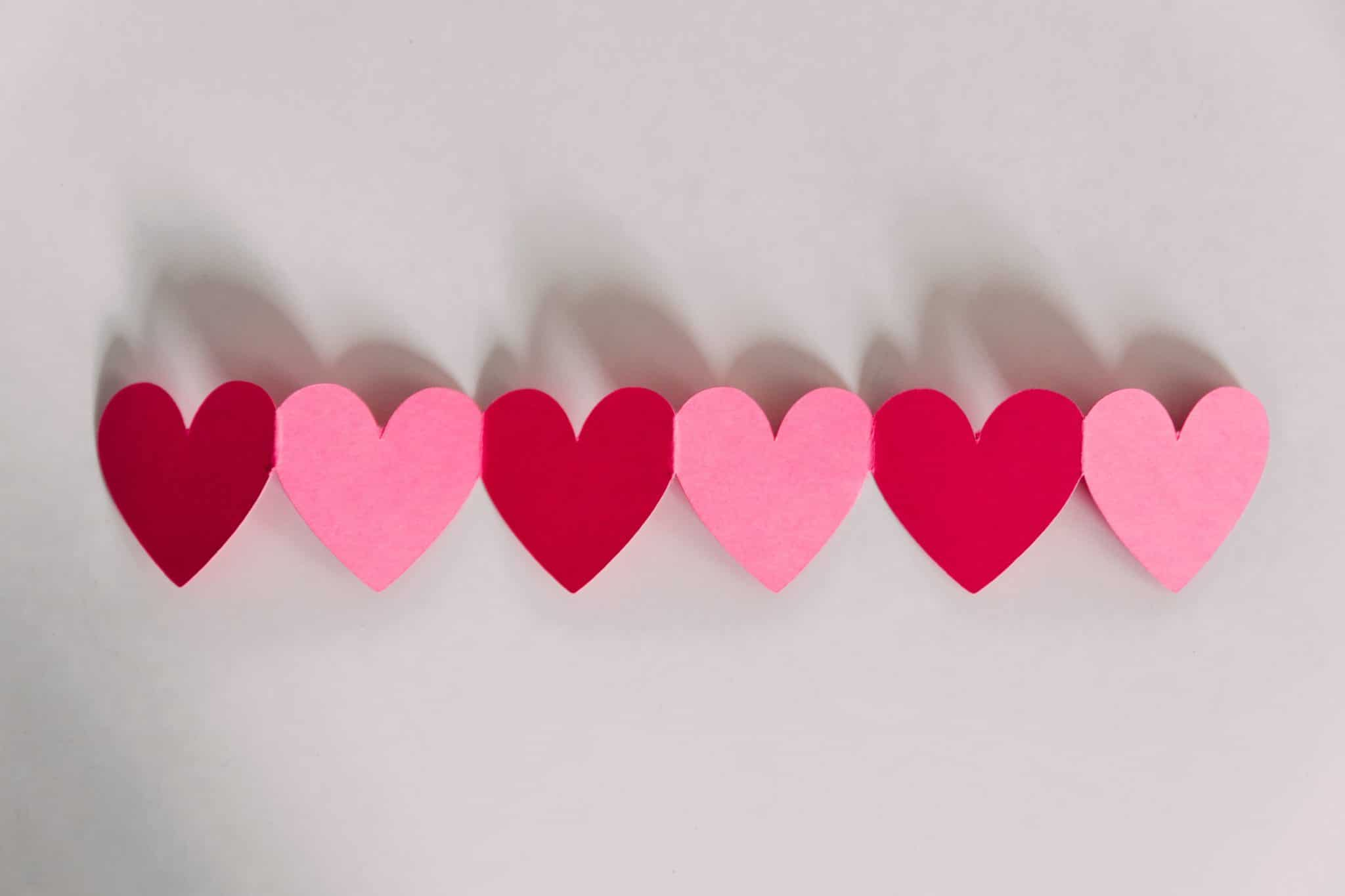 several red and pink paper hearts attached to eat other