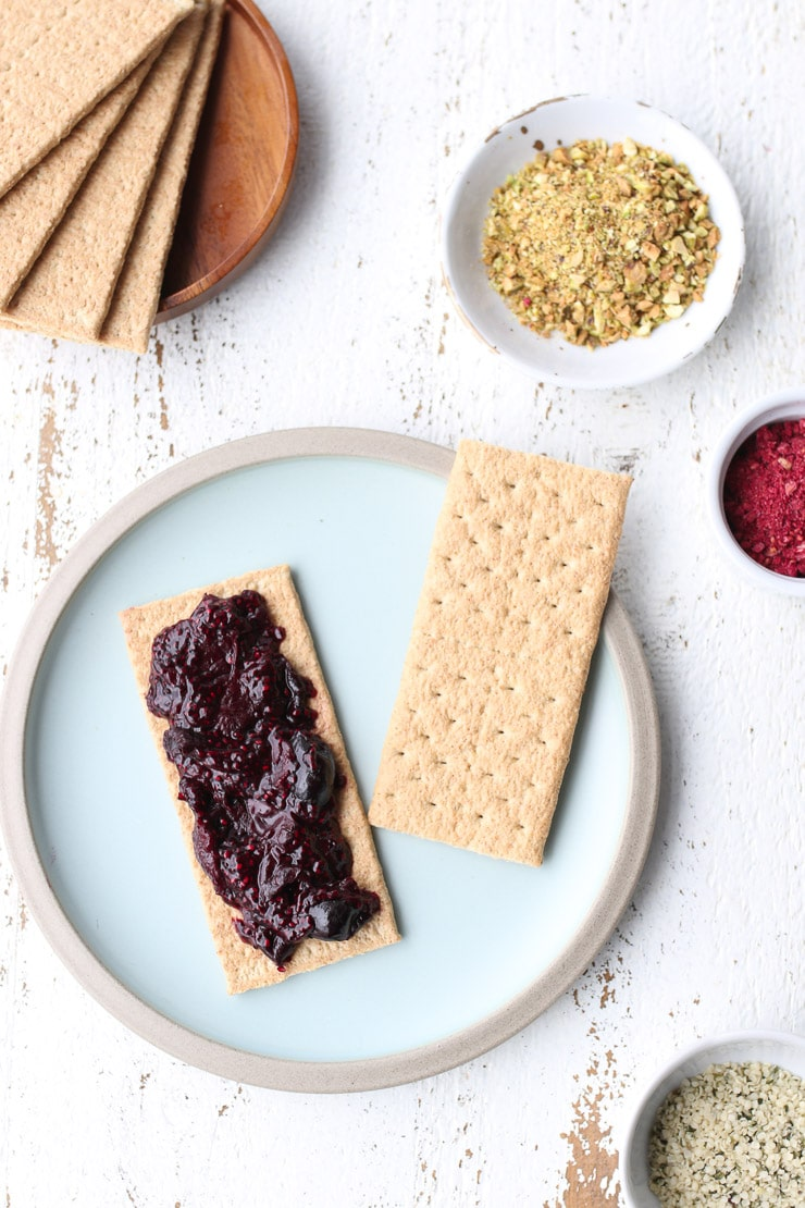 birds eye view of open faced pop tart with chia jam on a blue plate with extra garnished in the background