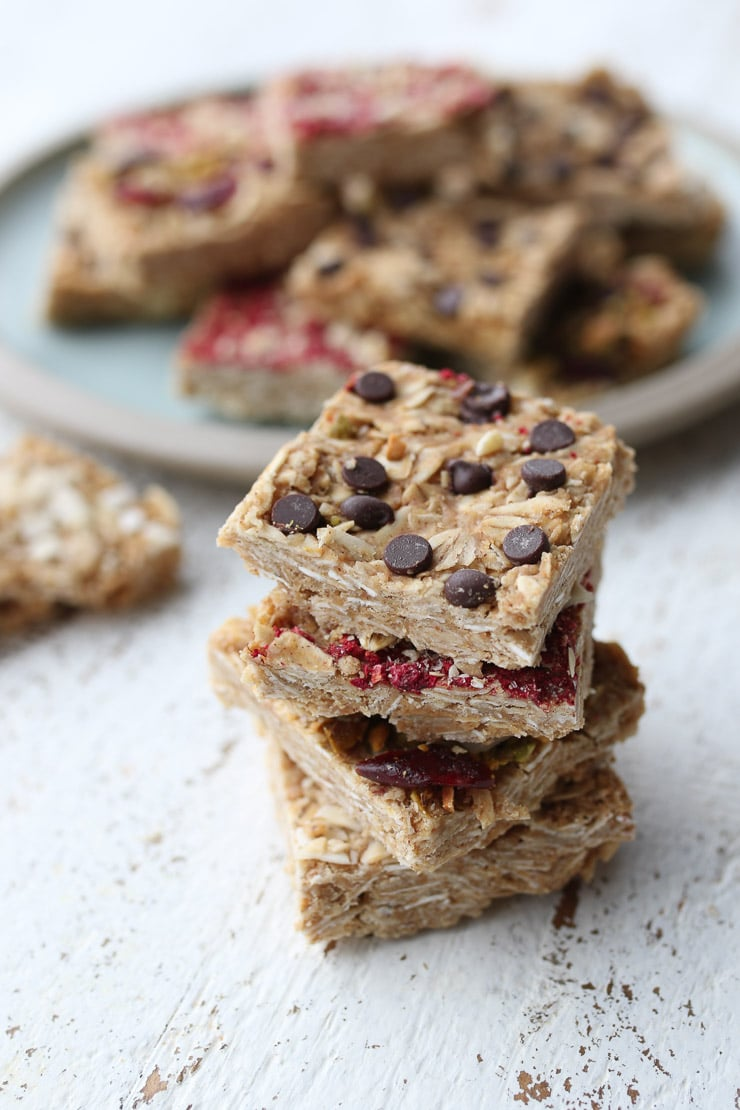 four oatmeal bars stacked on top of one another with a plate of oat bars in the background