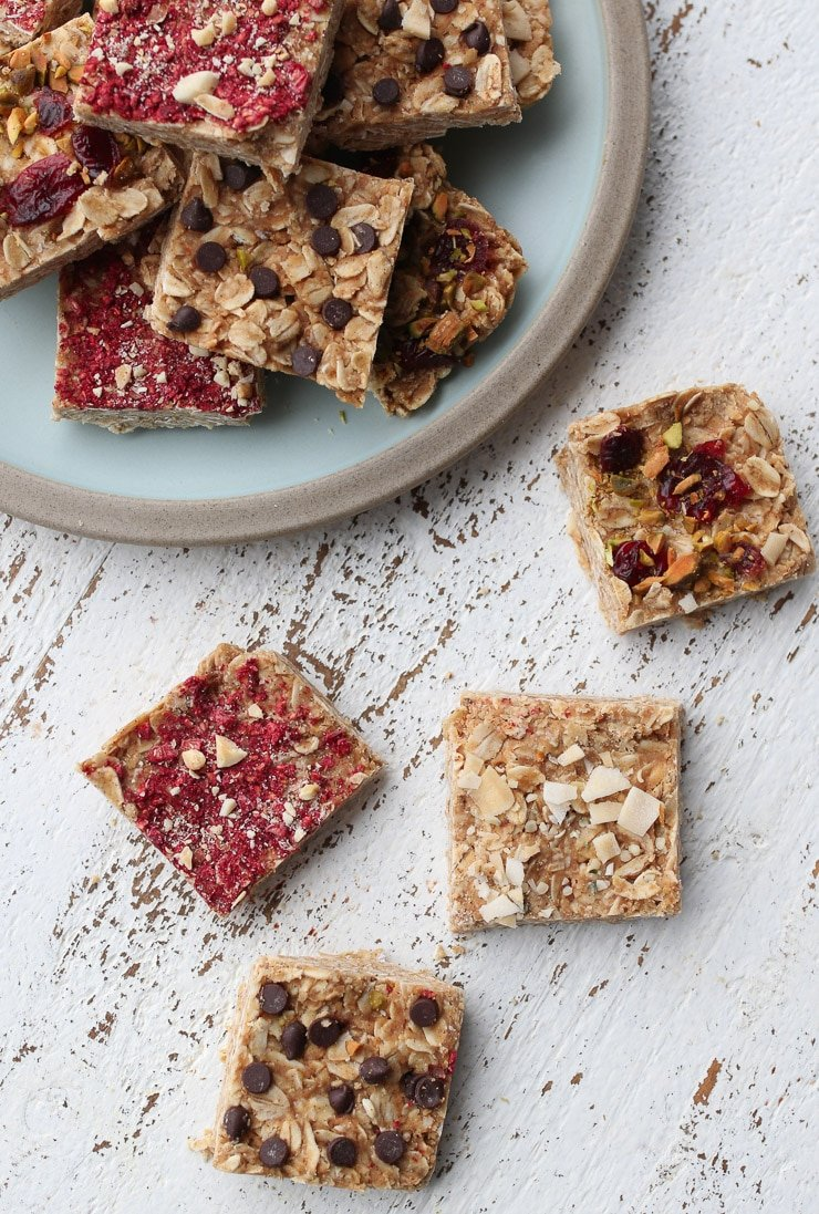 birds eye view of oatmeal bars with a variety of different topping like chocolate chips, coconut flakes, and freeze dried fruit
