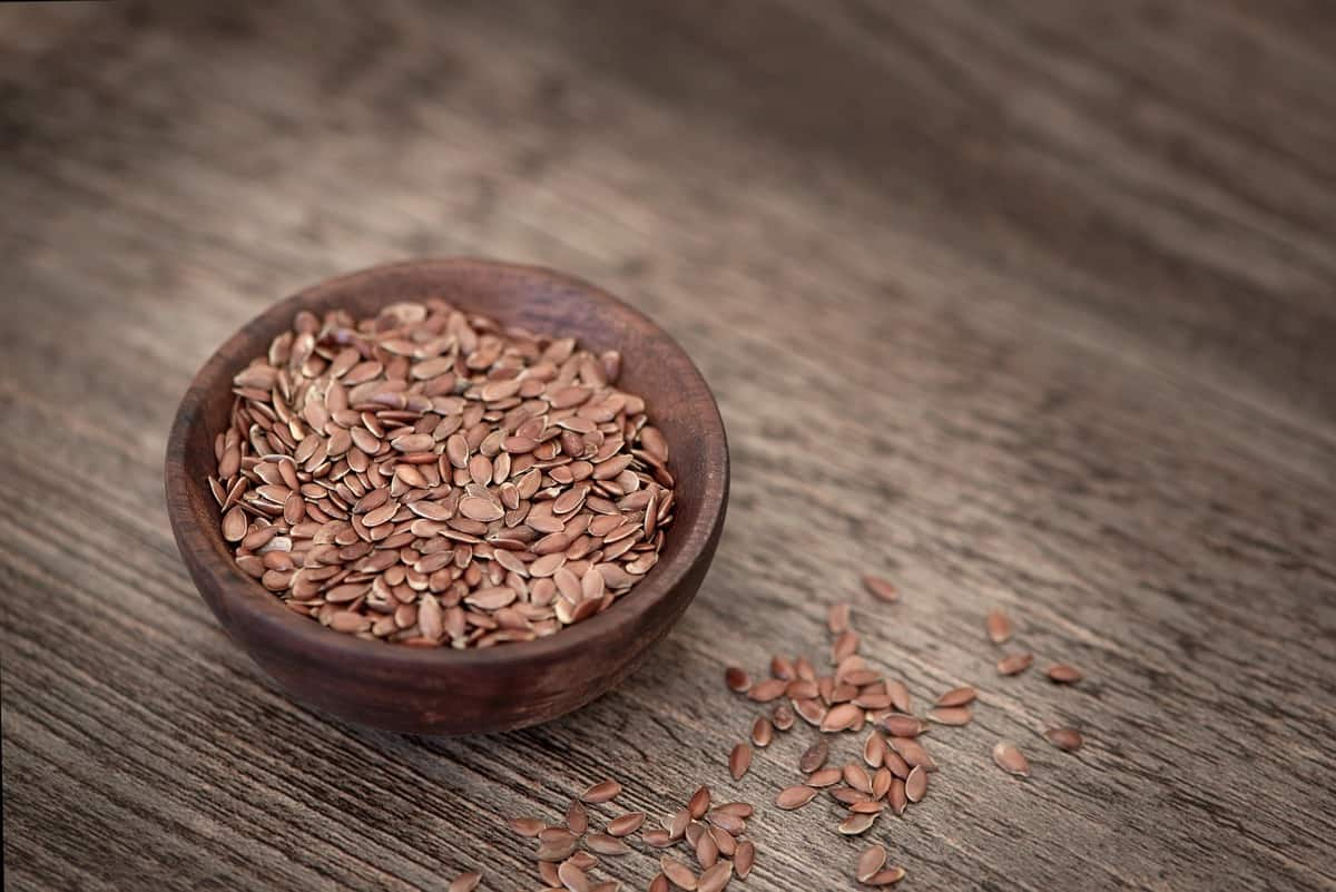 close up of whole flaxseed in a bowl for seed cycling