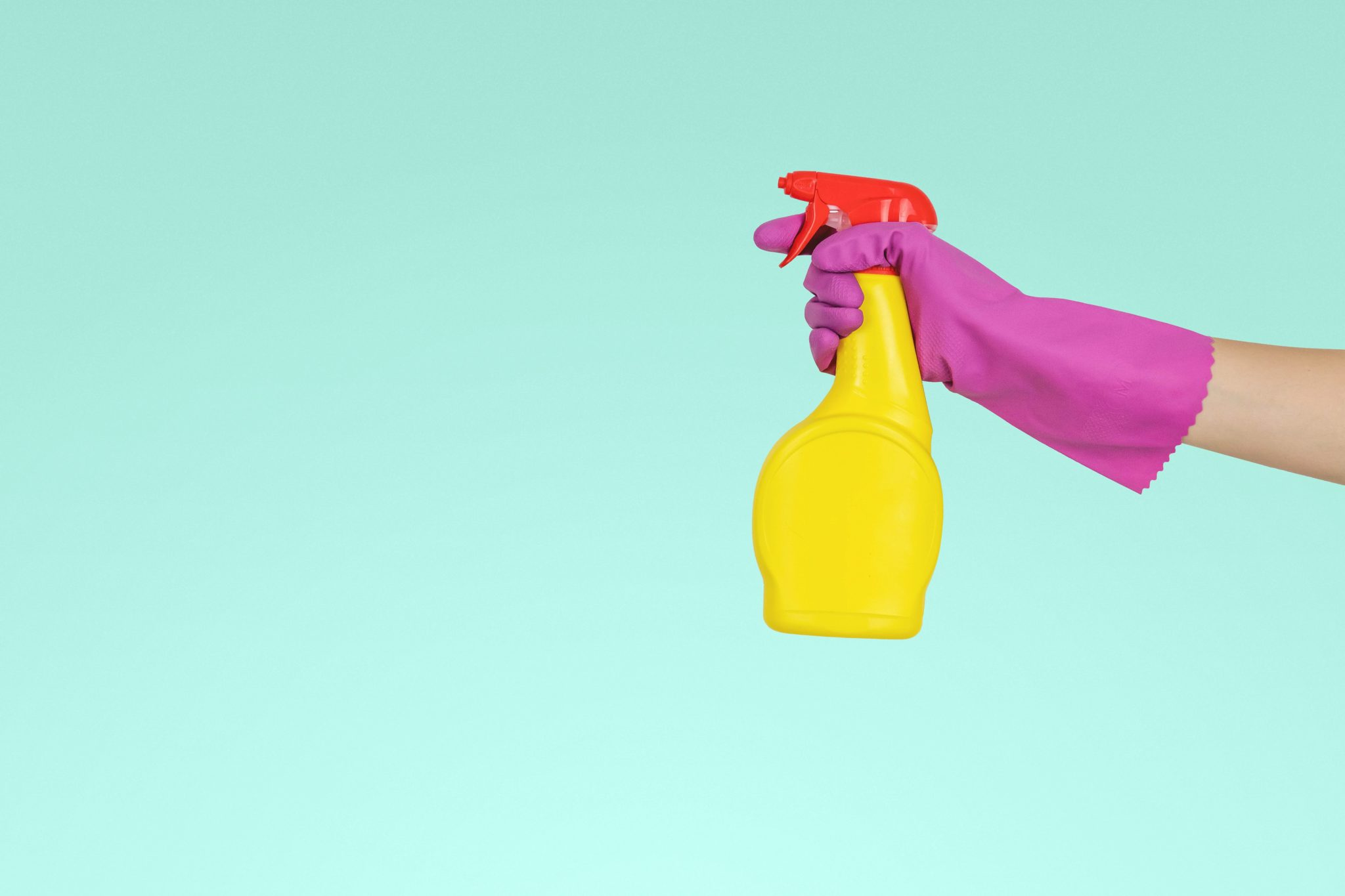 person wearing a purple glove and spraying a disinfectant in a yellow bottle