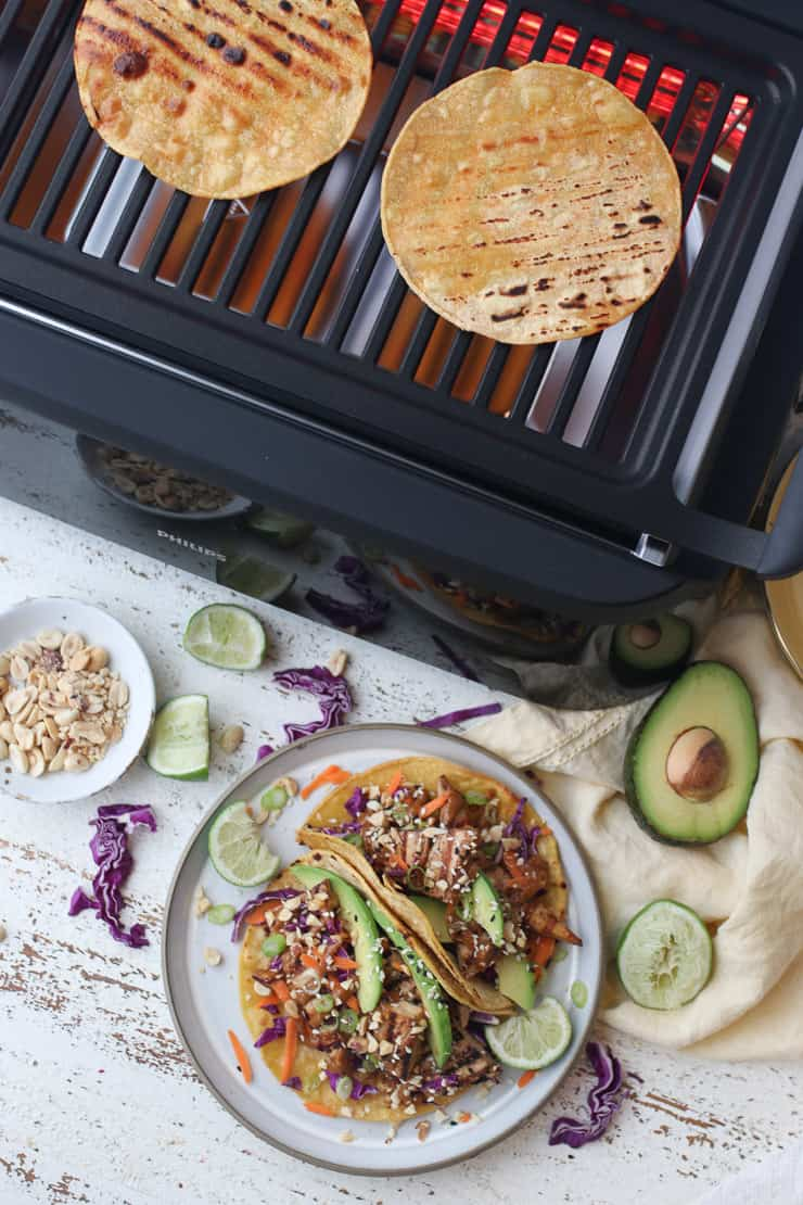 birds eye view of two tofu tacos on a plate with grill in the background grilling two tortillas