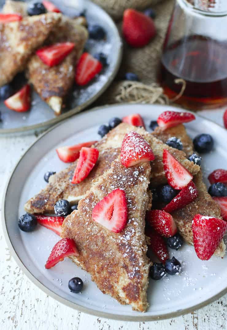 close up of tofu french toast on a white plate topped with berries