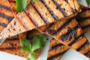 several pieces of grilled tofu on a white plate garnished with cilantro