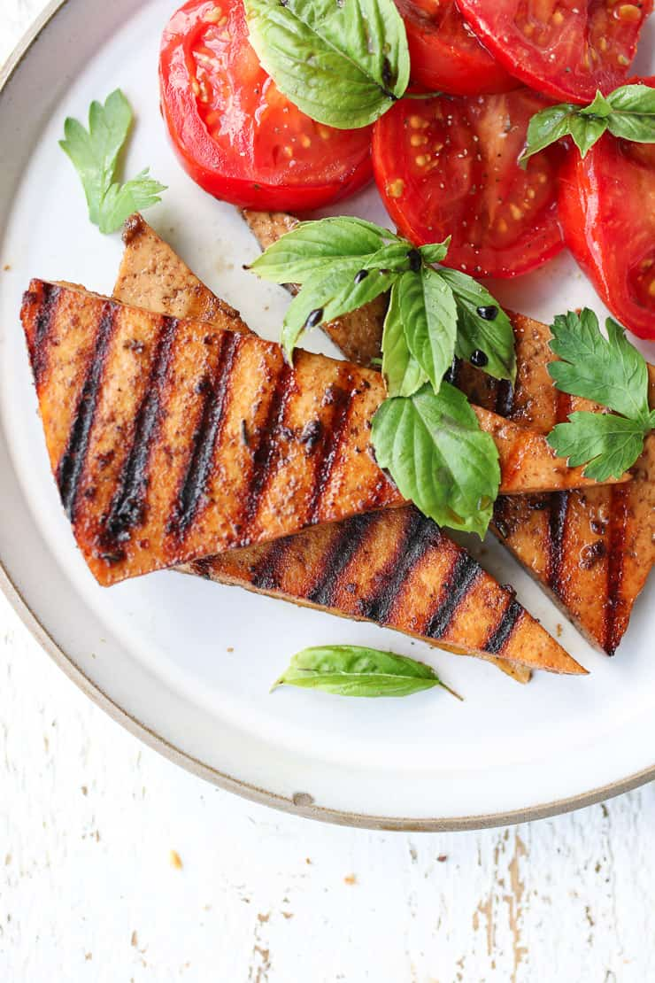 birds eye view of grilled vegan triangle steaks on a white plate with a side of tomato topped with fresh basil