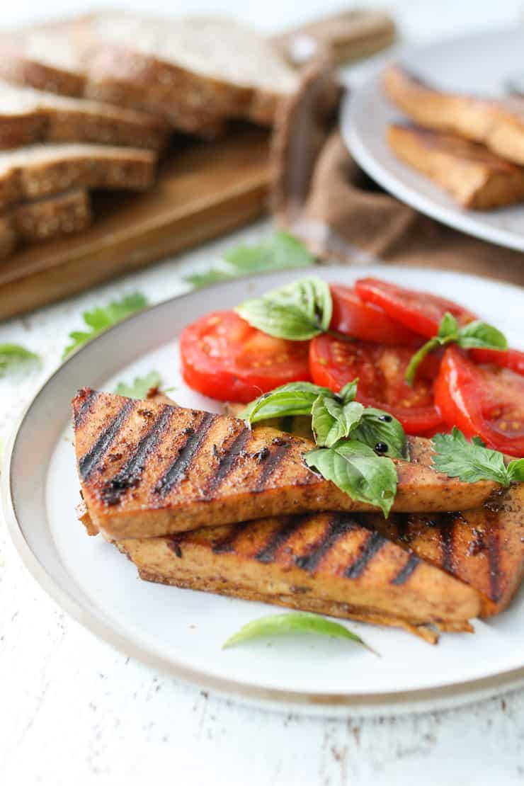 marinated grilled tofu on a white plate with tomatoes and basil on the side