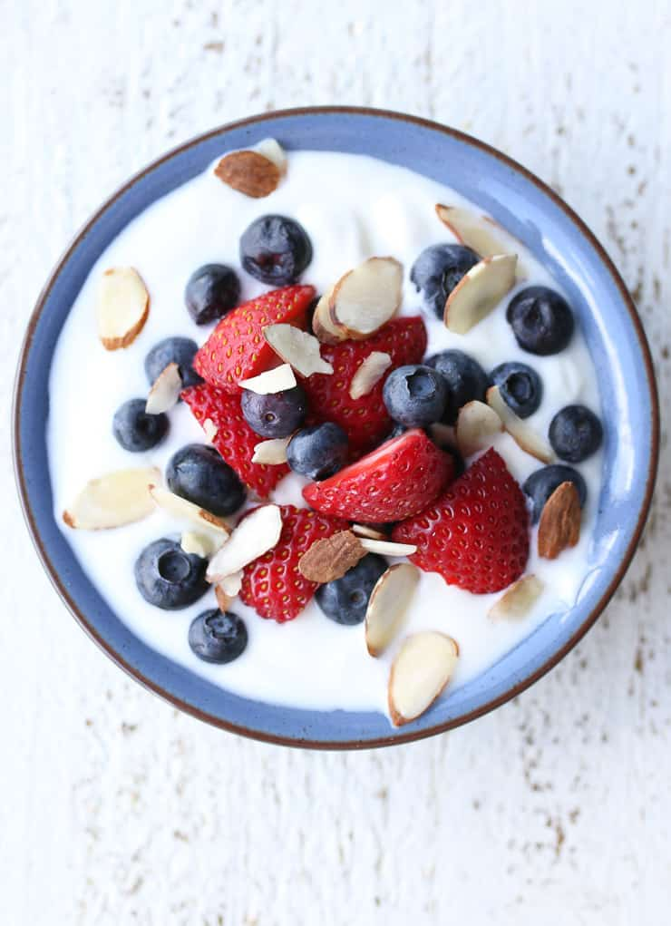 image of nuts, berries, and yogurt in a blue bowl as a healthy snack
