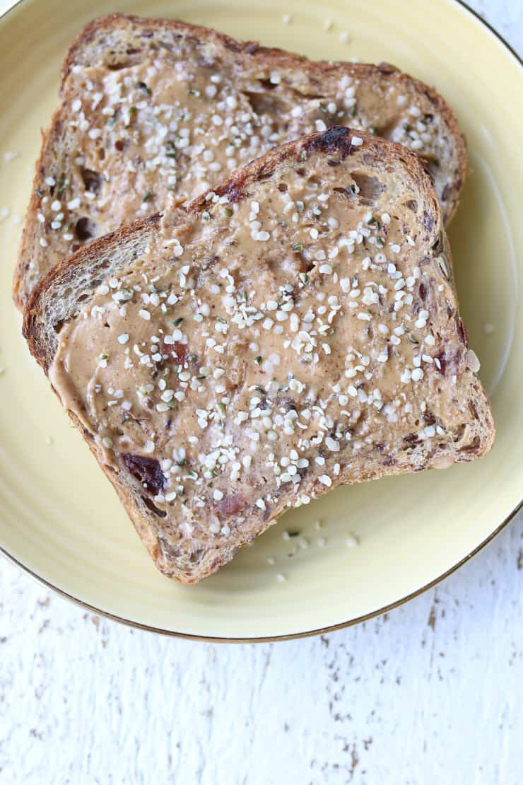 two pieces of toast with nut butter and hemp seed on a yellow plate