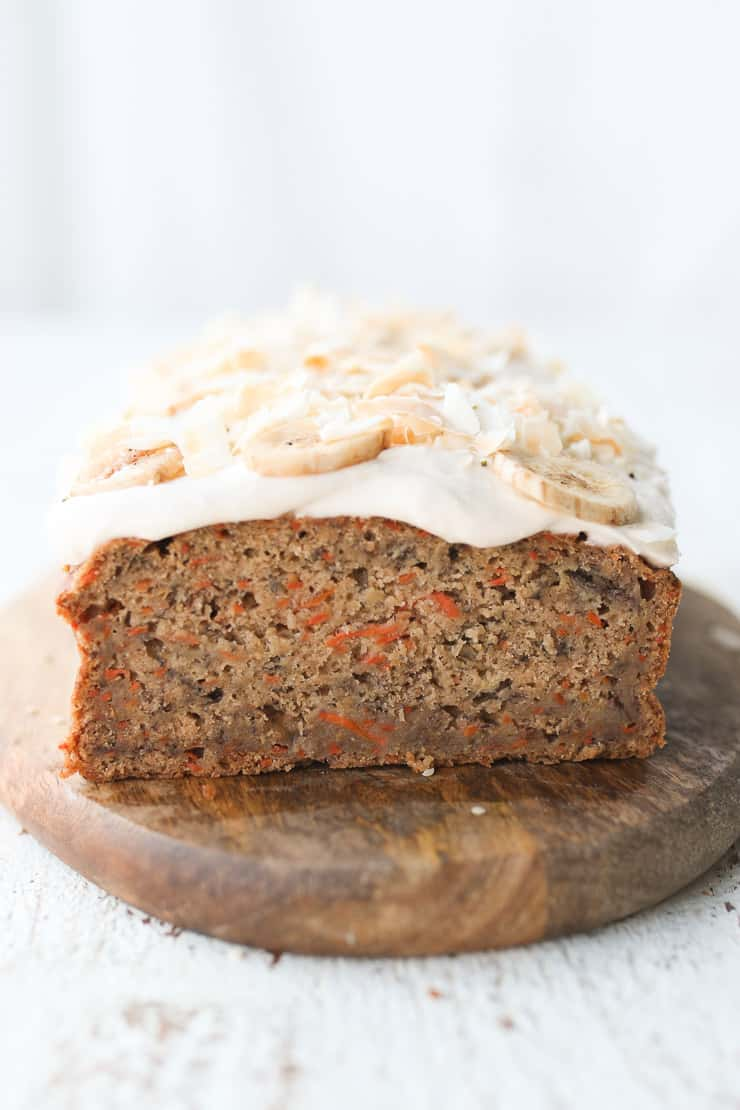 Banana Carrot Cake cut in half topped with cream cheese.