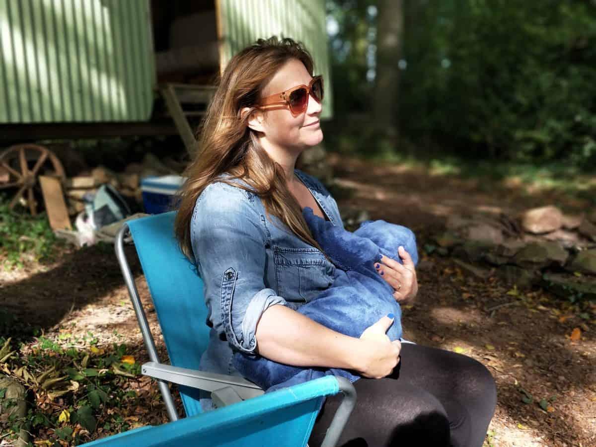 A woman sitting outside breastfeeding.