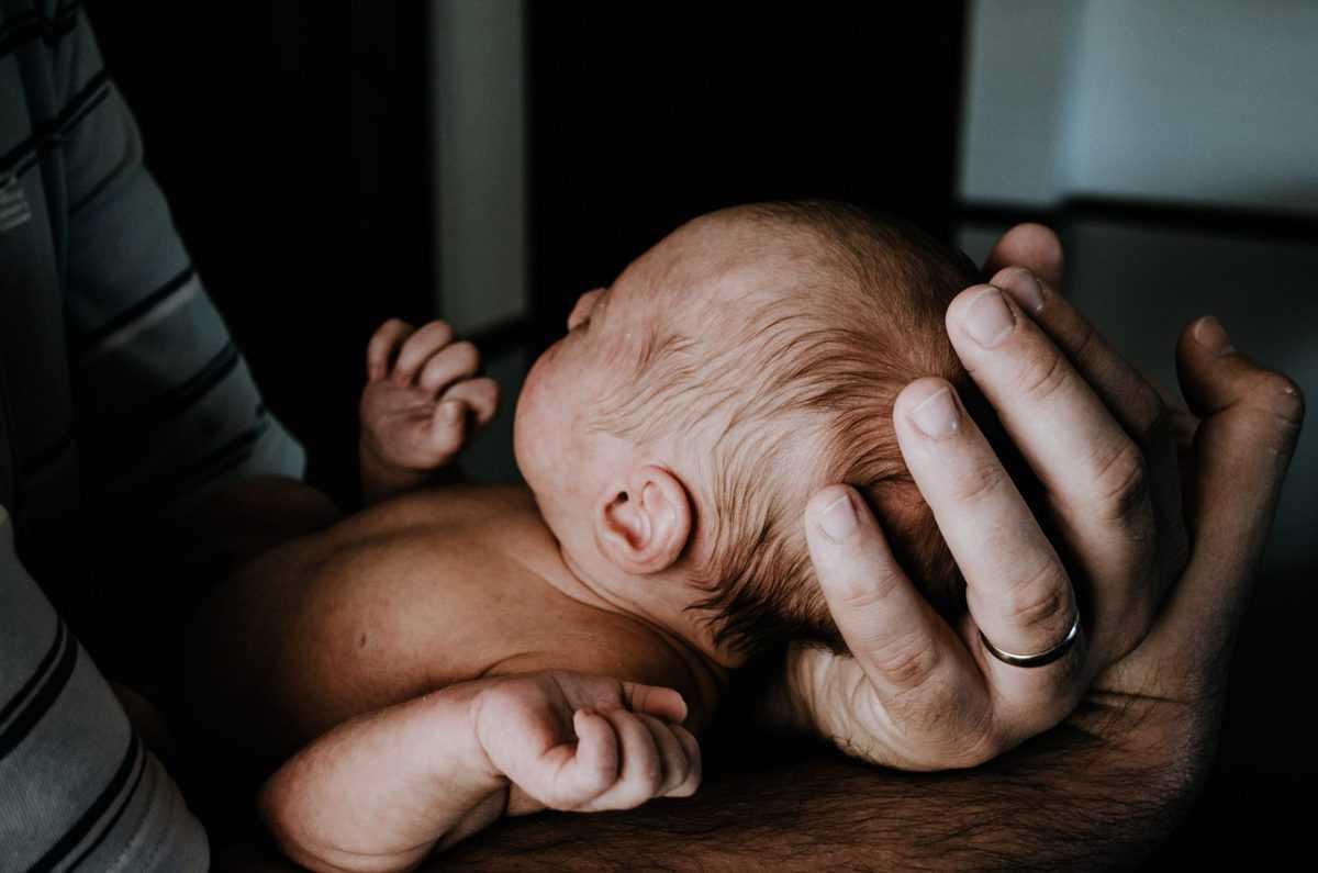 A newborn baby being held in someones hands.